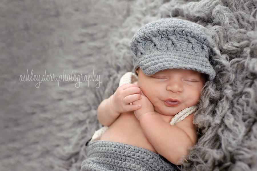newborn in newsboy hat and diaper cover