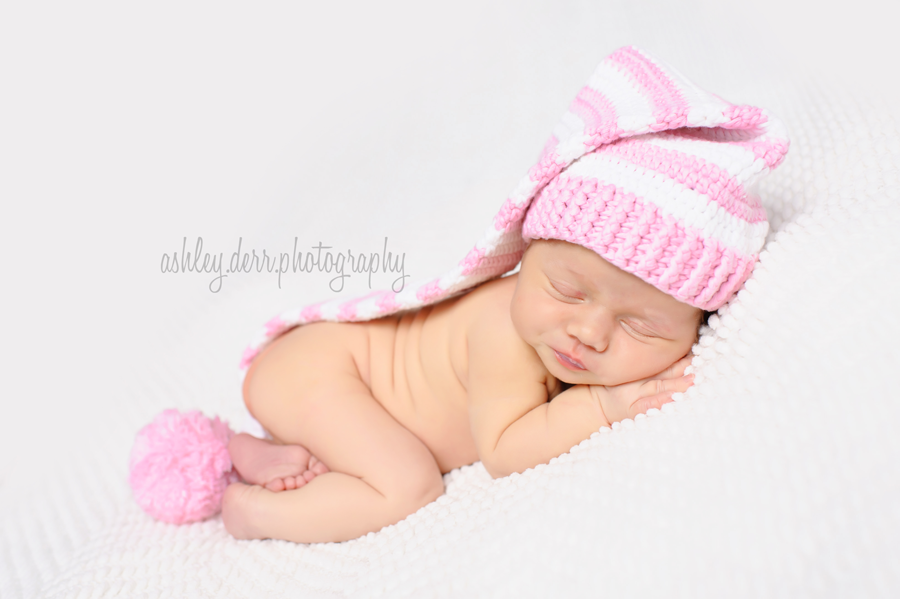 newborn baby girl on white with pink hat